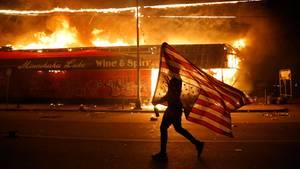Mensch mit amerikanischer Flagge vor brennendem Geschäft