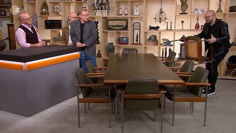 """""""Bares für Rares""""-Experte Sven Deutschmanek wuchtet die Möbel vonUlrich Wiechoczek und Wolfgang Hoffmeister in die Höhe, Moderator Horst Lichter schaut zu."""