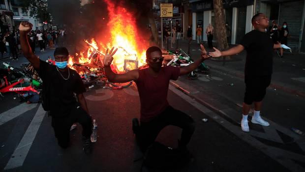 Frankreich, Paris: Demonstranten knien nieder und reagieren vor einer brennenden Barrikade.