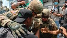 Soldaten gehen mit Demonstranten auf die Knie