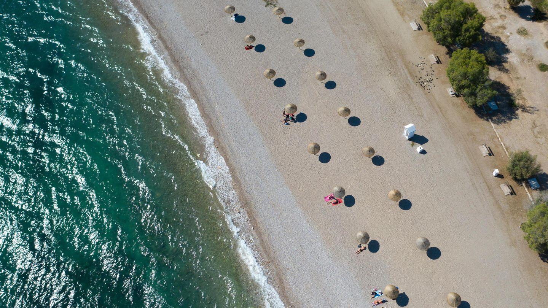 Griechenland: An einem Strandsüdlich von Athen stehen Sonnenschirme für Strandbesucher bereit