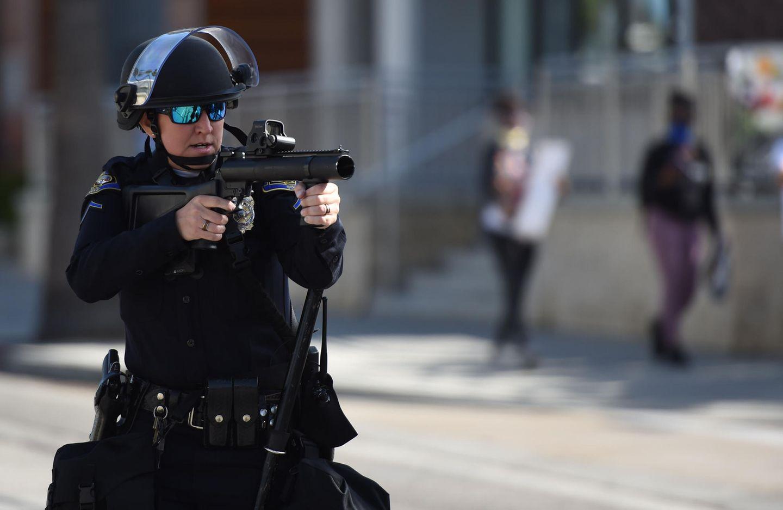 Polizist zielt mit Gummigeschoss