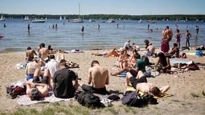 Sonnenhungrige in Berlin genießen das gute Wetter an einem Strand der Badebucht Am Großen Fenster an der Havel