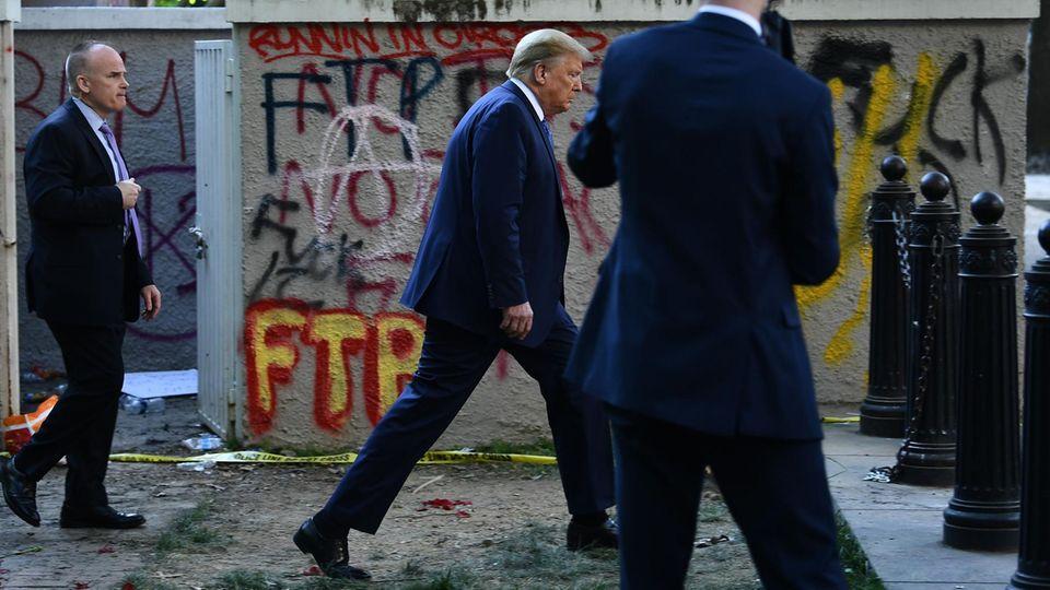 Donald Trump spaziert nach dem Besuch einer Kirche entlang einer mit Graffiti besprühten Mauer zurück ins Weiße Haus
