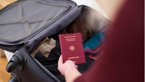 Von einer Person ist nur der linke Arm zu erkennen, der einen deutschen Reisepass in einen aufgeklappten Koffer legt