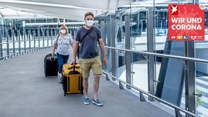 Wir und Corona: Reisende mit Koffer und Mundschutz