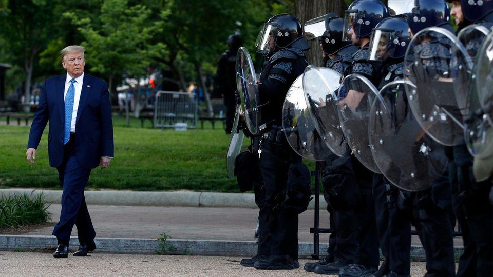 USA, Washington: Donald Trump (l.), Präsident der USA, geht im Lafayette Park an Polizisten vorbei