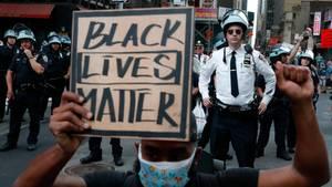 USA, New York: Polizisten beobachten Demonstranten, die an einem Solidaritätsmarsch für George Floyd teilnehmen