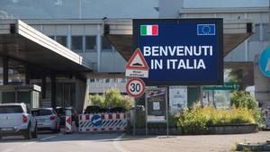 """""""Benvenuti in Italia"""" ist an der Grenze zwischen der Schweiz und Italien auf einer Monitorwand zu lesen"""