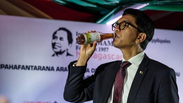 Madagaskars Präsident Andry Rajoelina nimmt einen Schluck vom angeblichen Heilmittel während einer Pressekonferenz im April