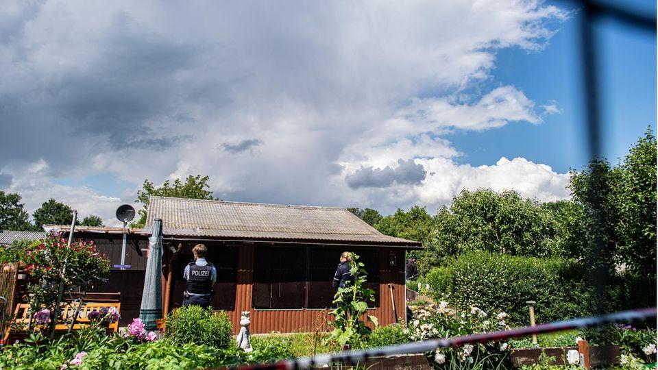 zwei Polizeibeamte an der Rückseite der Gartenlaube