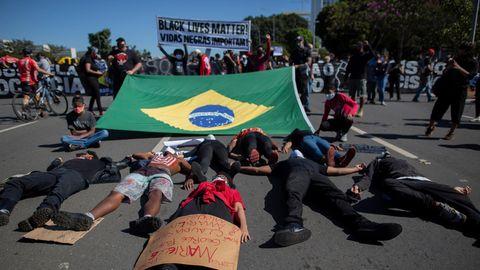 Brasilien: Junge Schwarze liegen hinter der Landesfahne auf dem Boden und symbolisieren den Tod schwarzer Menschen