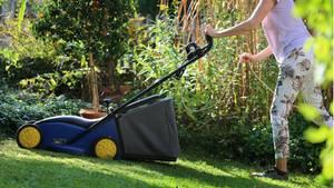Rasen mähen: Frau mäht den Rasen in einem Garten