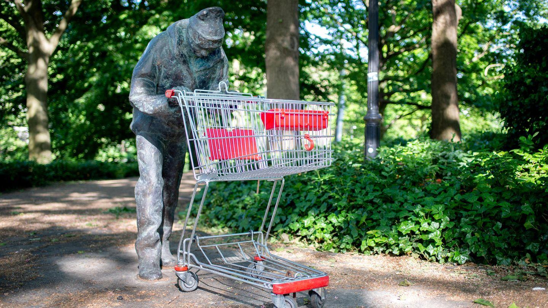 Eine Bronzefigur mit einem Einkaufswagen in den Händen steht in den Wallanlagen im Zentrum Bremens
