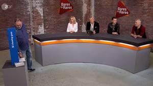 """""""Bares für Rares""""-Händler Walter """"Waldi"""" Lehnertz nimmt den Kaugummiautomaten in Augenschein. Susanne Steiger, Markus Wildhagen, Fabian Kahl und Christian Vechtel bleiben sitzen."""