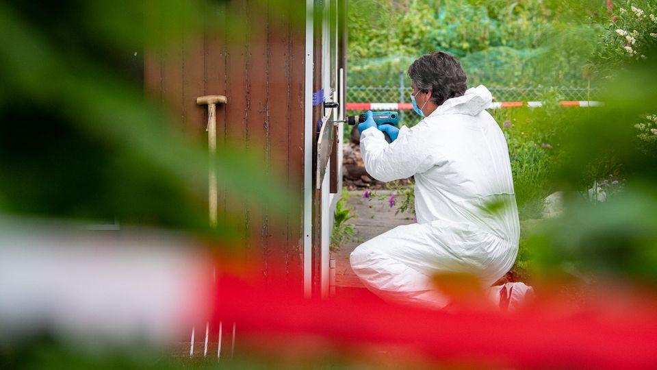 Ein Mann in weißem Overall kniet vor einer Gartenlaube und bohrt mit einer Bohrmaschine offenbar die Tür auf