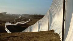 Ein aus weißem Tuch gespannter, geschwungener Zaun