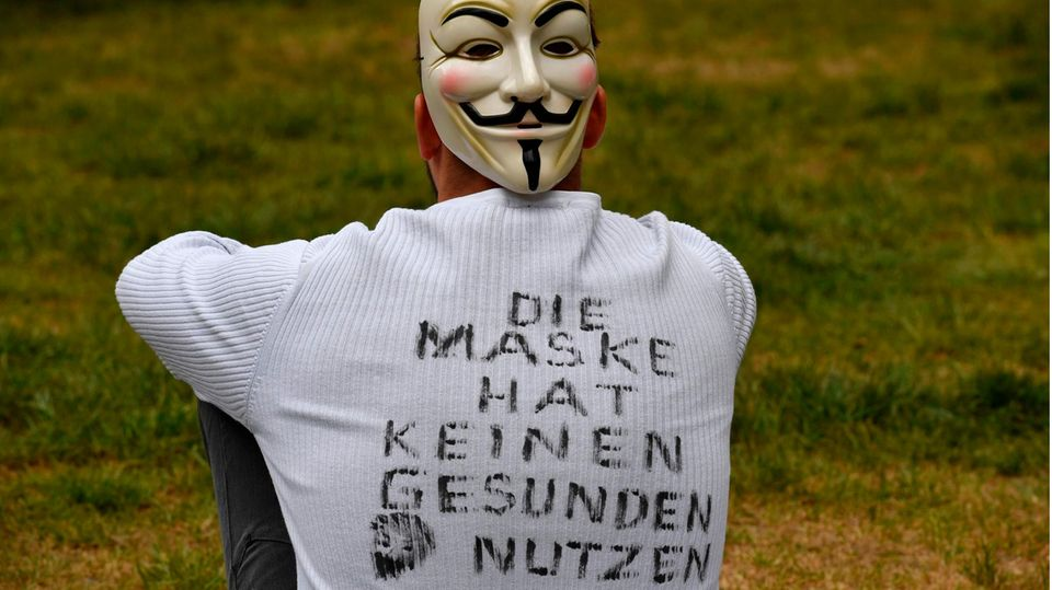 """Ein junger Mann sitzt auf einer Wiese und hat """"Die Maske hat keinen gesunden Nutzen"""" auf dem Rücken geschrieben"""