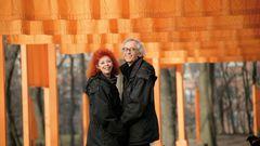 Das Paar steht lächelnd vor organgefarbenen Tüchern im Central Park in New York