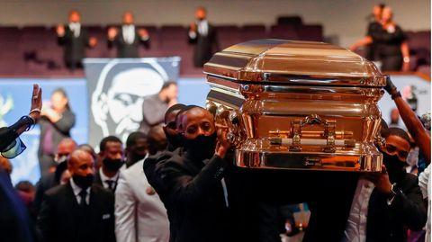 Männer in schwarzen Anzügen tragen einen goldglänzenden Sarg aus einer vollen Kirche