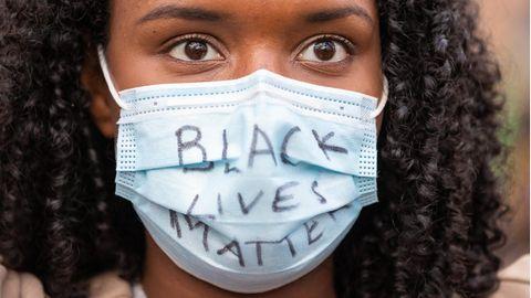 """Auf dem Mundschutz einer schwarzen jungen Frau steht """"Black Lives Matter"""""""
