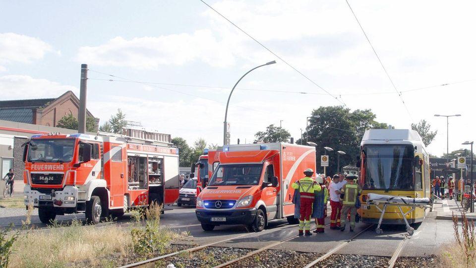 Einsatzkräfte der Feuerwehr stehen neben einer Straßenbahn.