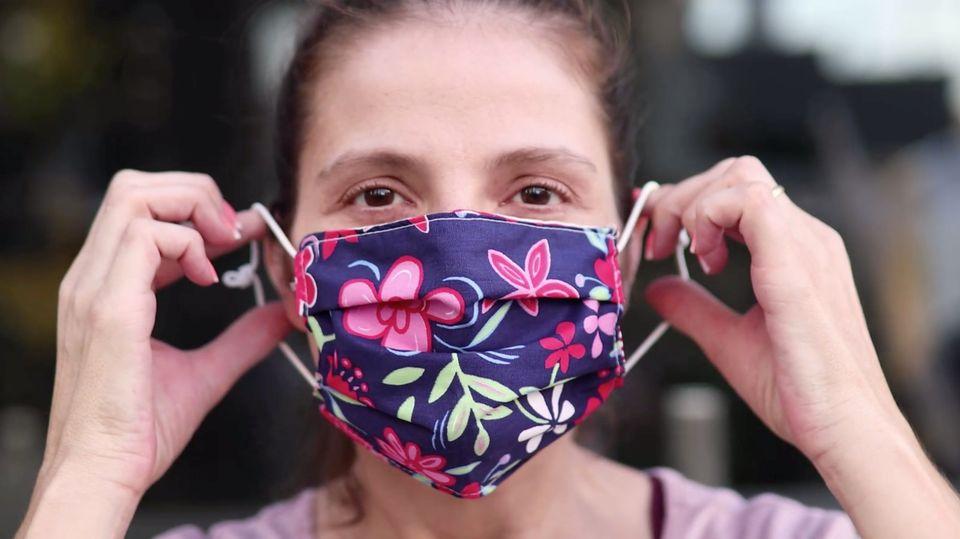 Frau zieht eine Atemschutzmaske über