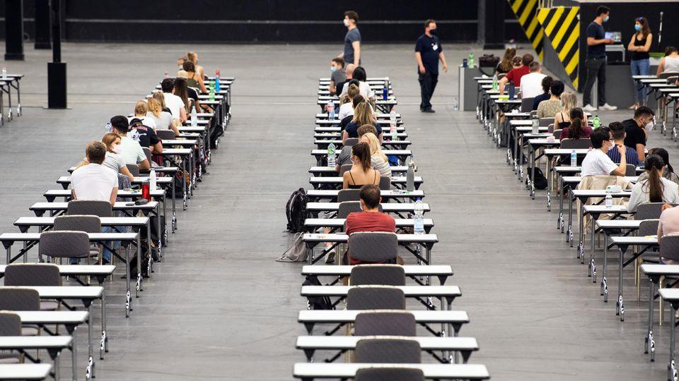 Studenten sitzen an Tischen mit großem Abstand