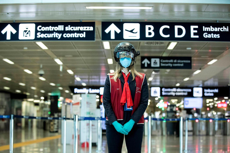 Die neue Normalität an Flughäfen weltweit:: Eine Mitarbeiterin des Flughafen Leonardo da Vinci in Rom trägt den neuen Smart Helmet zur automatischen Messung der Temperatur von Passagieren.