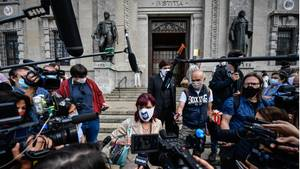 Vor einem mit Statuen geschmückten Gebäude sammeln sich Reporter mit Mikrofonen um eine Frau mit weißer Gesichtsmaske