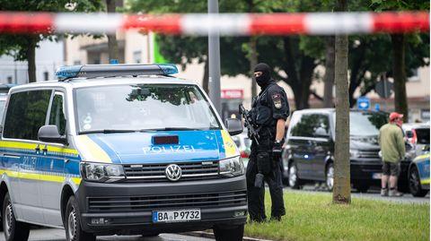 Neben einem VW-Bus der Polizei steht ein Polizist mit Maschinenpistole und Sturmhaube