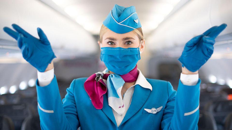 Sicherheitsanweisung mit Fingerzeig auf die Notausgänge: Diese Flugbegleiterin trägt einenMund-Nasen-Schutz.