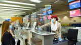 Arbeitsplatz Check-in: Die Mitarbeiterin am Flughafen Dubai wird durch eine Plexiglaskonstruktion am Counter geschützt.