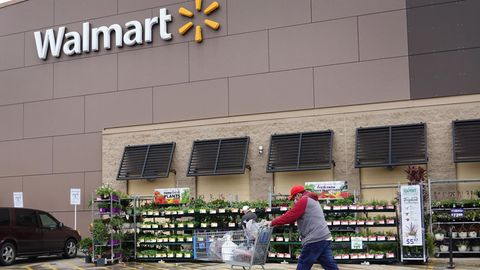 Ein Mann mit Einkaufswagen läuft vor einer Walmart-Filiale