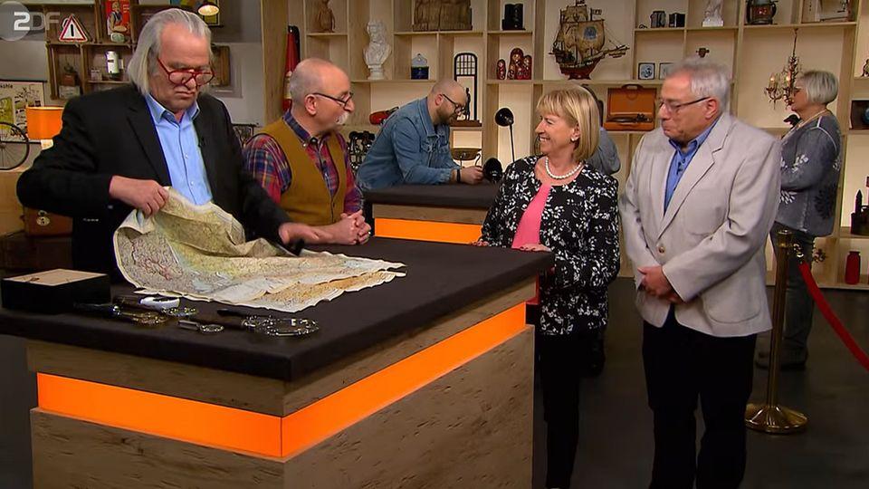 """""""Bares für Rares""""-Experte Albert Maier nimmt die Stofflandkarten von Ehepaar Roth in Augenschein, Moderator Horst Lichter plaudert mit den Verkäufern."""