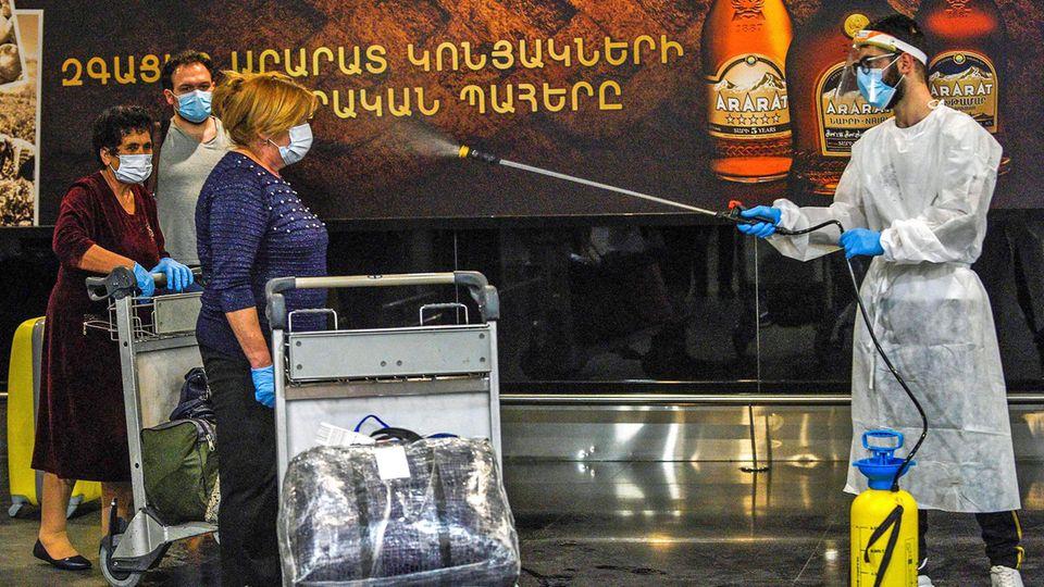 Bild 1 von 20der Fotostrecke zum Klicken:Willkommen in der neuen Welt des Reisens. Nach Ankunft in Armenien müssen sich Fluggäste in Jerewan vom Airport-Personal desinfizieren lassen.