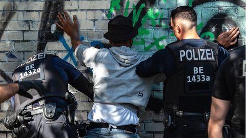 Polizeibeamte kontrollieren in einem Berliner Park einen Mann mit dunkler Hautfarbe als mutmaßlichen Drogendealer