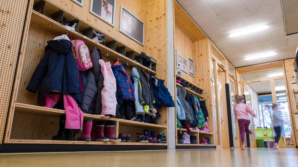 Zwei Mädchen laufen an einer Garderobe voller Kinderjacken vorbei