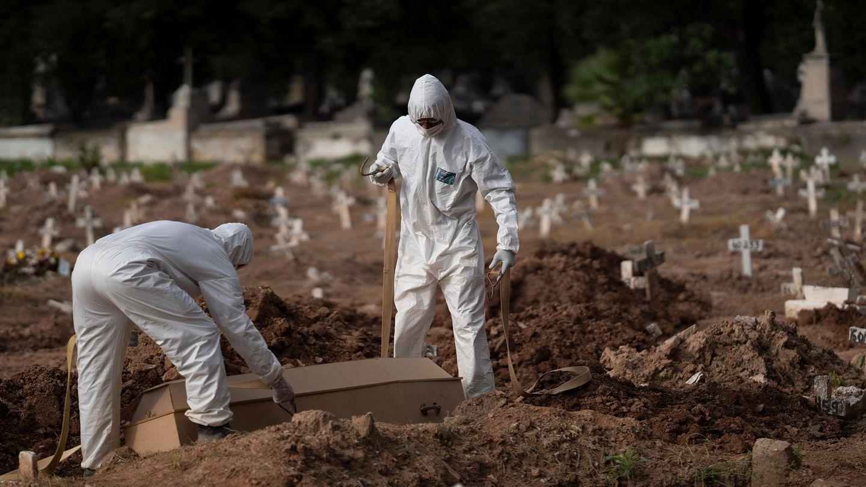 Brasilien, Rio De Janeiro: Friedhofsmitarbeiter in Schutzkleidung vergraben einen Sarg