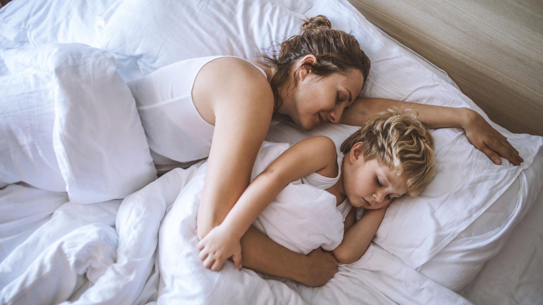 Mutter und Sohn schlafen im Bett