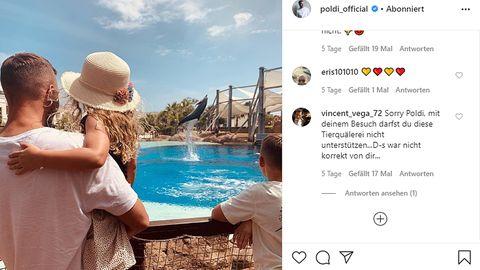Lukas Podolski schaut mit seinen Kindern einem Delfin in Gefangenschaft zu