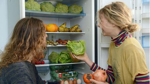 """Lenny (l) und Freja nehmen Obst aus ihrem Kühlschrank, das sie aus den Abfallbehältern eines Supermarktes """"gefischt"""" haben."""