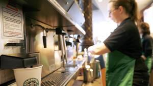 Mitarbeiterin von Starbucks macht einen Kaffee