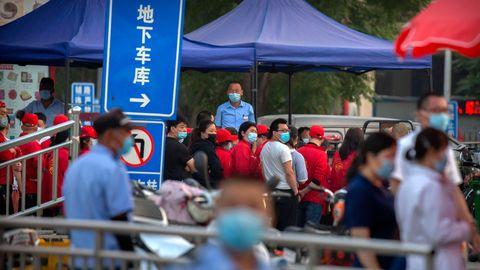 Polizisten sichern einen Fleischmarktin Peking, der von den Behörden geschlossen wurde, nachdem bekannt geworden war, dass ein Besucher des Marktes positiv auf das Coronavirus getestet worden war.