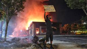 Ein Mann hält ein Schild, während im Hintergrund das Wendy's-Restaurant in Atlanta brennt.