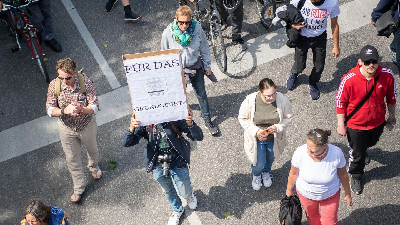 """Ein Mann hält während einer Demonstration ein Schild, auf dem """"Für das Grundgesetz"""" steht, hoch"""