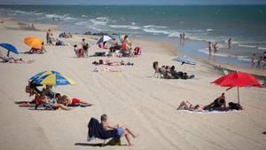 Menschen liegen und baden am Strand