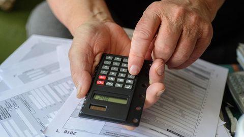 Ein Mann tippt angesichts der fälligen Steuererklärung in seinen Taschenrechner
