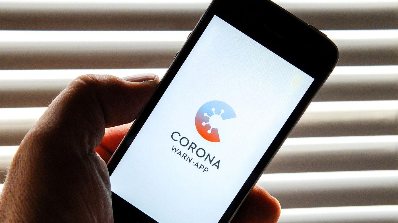 Auf dem Bildschirm eines Smartphones ist der Startschirm einer Corona-Warn-App zu sehen