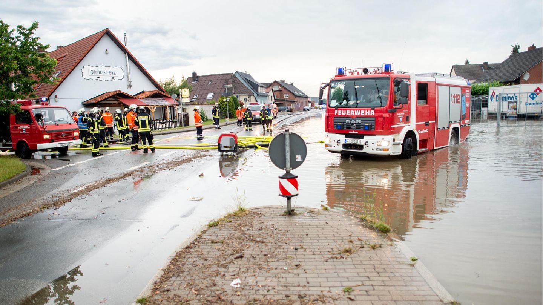 Ein Einsatzfahrzeug der Feuerwehr steht auf der überschwemmten und gesperrten Bundesstraße B188 im Landkreis Gifhorn vor einem Supermarkt, dessen Parkplatz durch Starkregen überflutet wurde